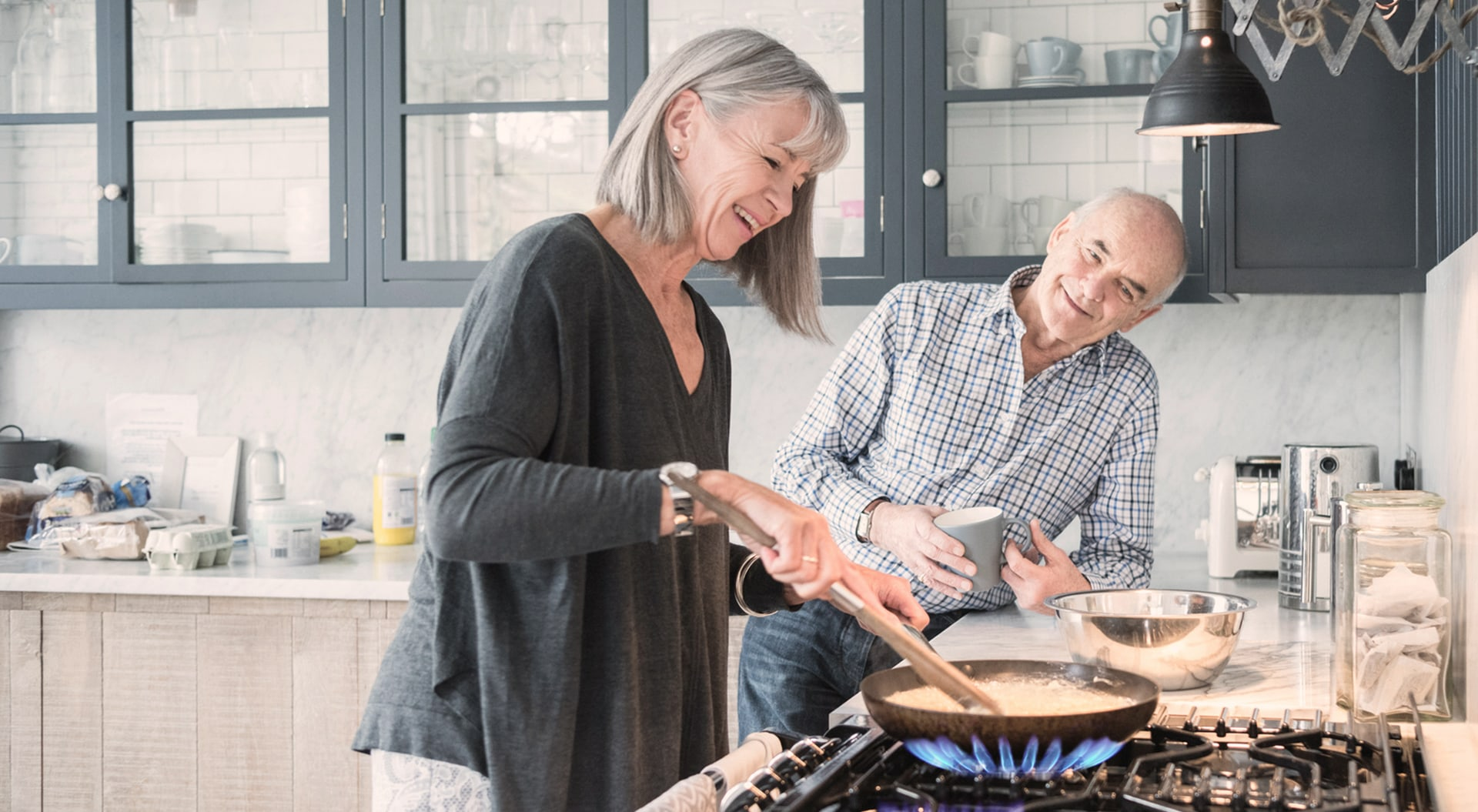 elderly couple cooking on a gas stove