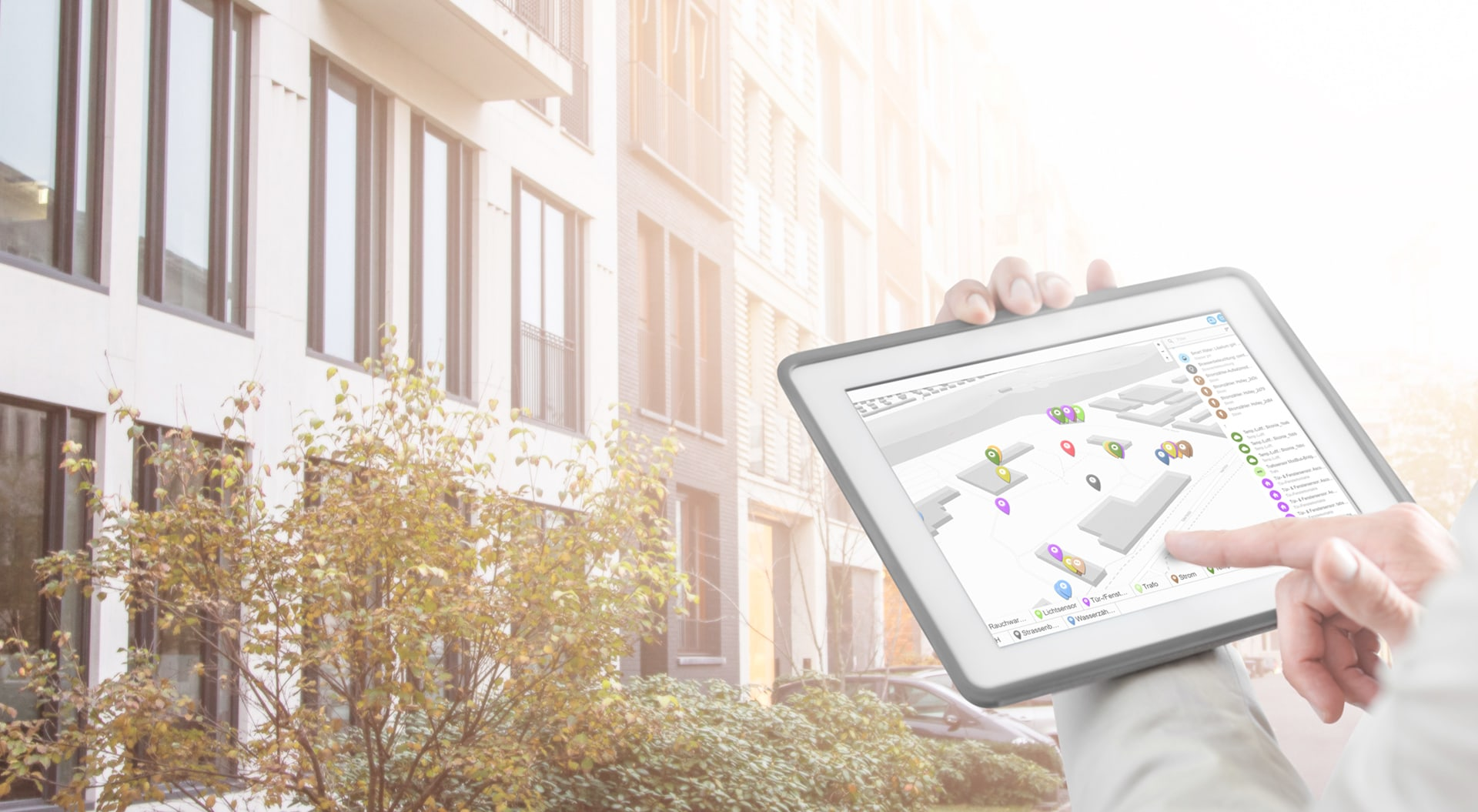 tablet with sensor visualisation in front of a building